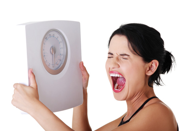 frustrated woman holding a scale