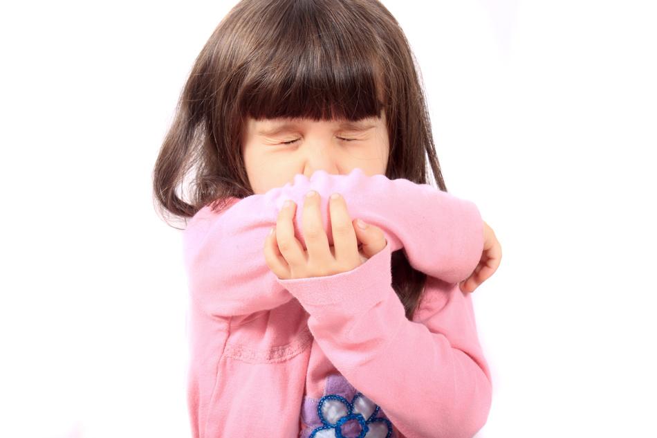 Little sick girl sneezing onto her sleeve