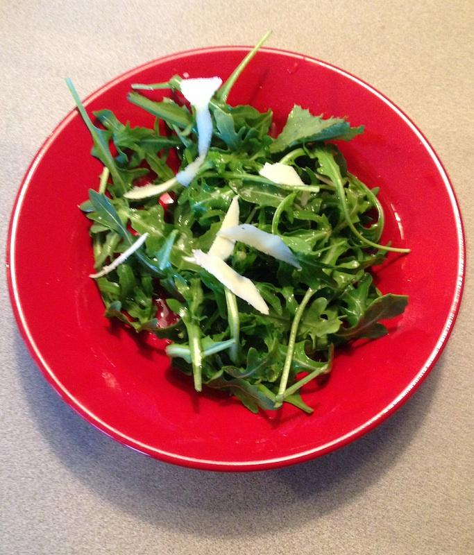 Arugula salad on red dish