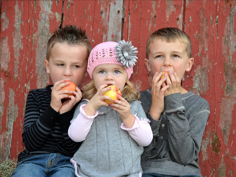 Three children eating apples