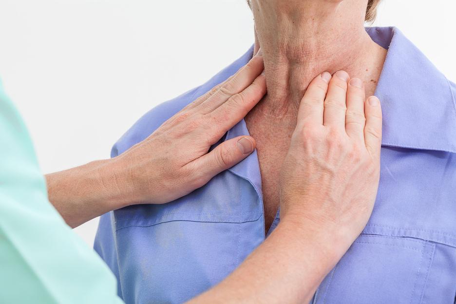 Nurse examining woman's thyroid