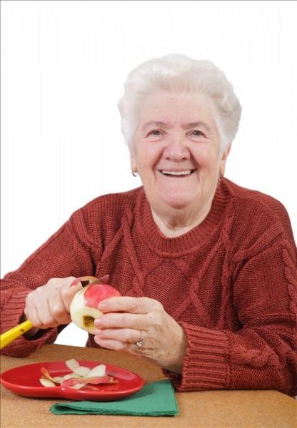 Older woman paring an apple