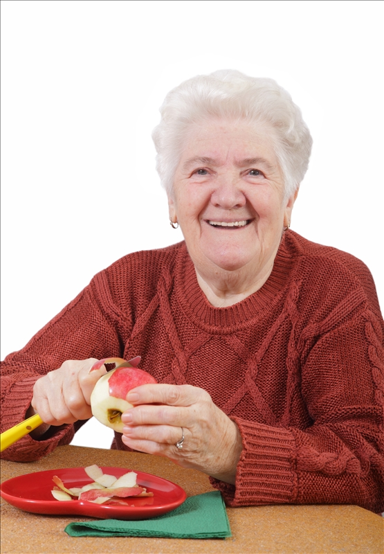 Older woman paring an apple