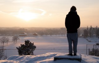 Man watching winter sunset