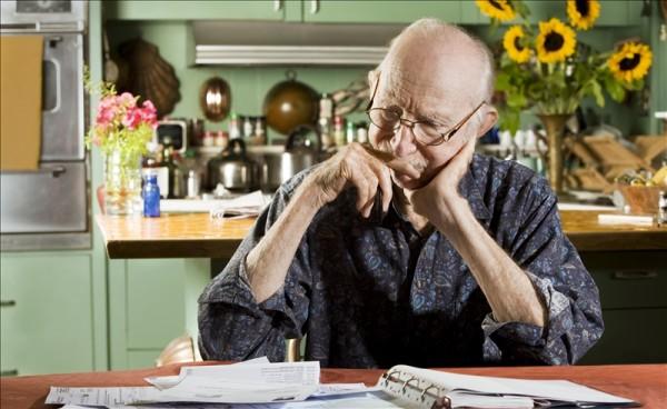 Elderly man looking at bills