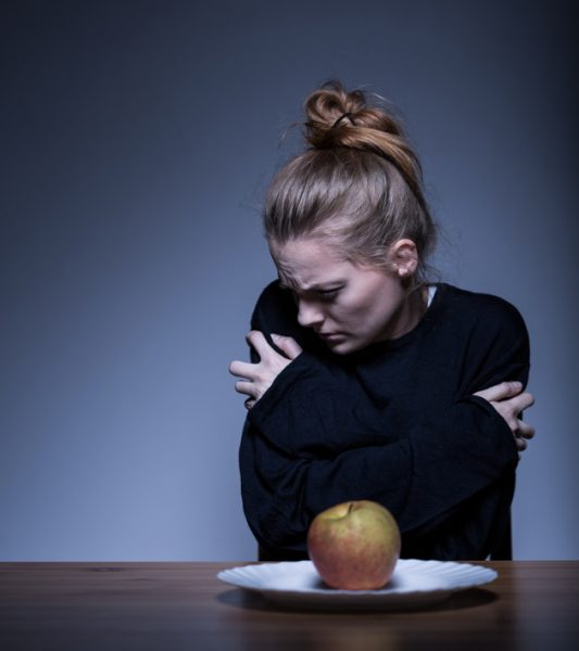 Image of a despair female suffering from food addiction