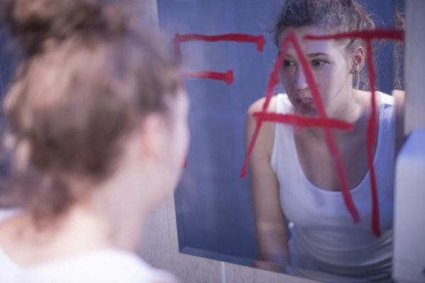 Fat red writing on mirror and teenage girl, food addiction/Source: Pond5