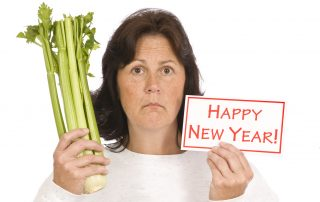 Unhappy woman showing celery and happy new year sign/resolutions