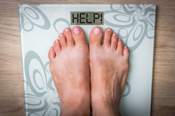 Woman's feet on a scale with word HELP! Food addiction