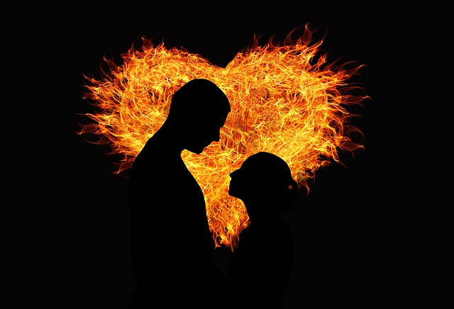 Silhouette of two people against a flaming heart of love