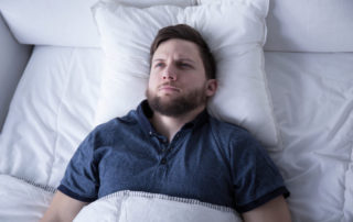 man suffering from insomnia lying in bed