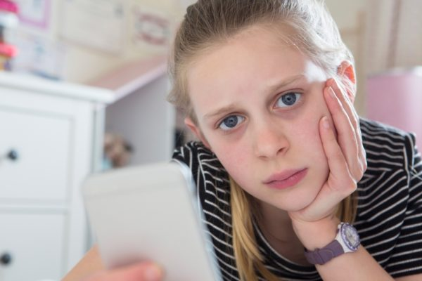Young girl looking at phone/cyberbullying