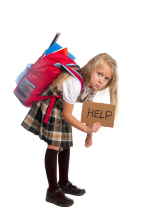 Little girl with heavy backpack