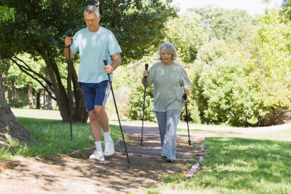 Older couple using walking sticks
