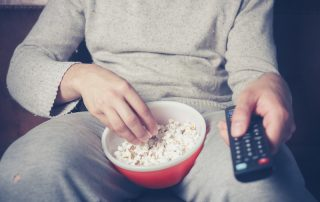 Person on couch eating popcorn and holding a remote