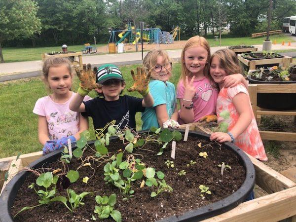 Kids planting at multigenerational garden