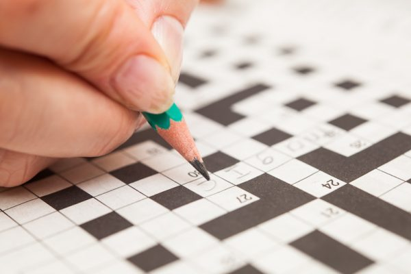 person doing crossword puzzle/Adobe stock