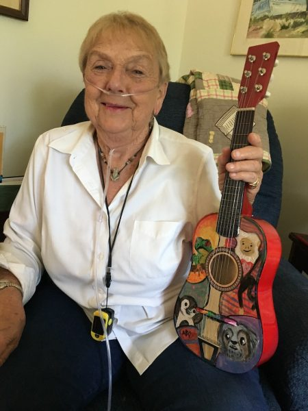 Joanne Santee holding the guitar her granddaughter painted