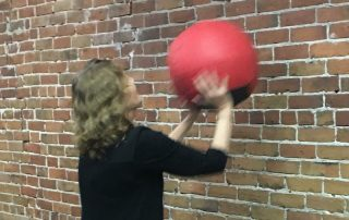 Diane Atwood slamming medicine ball against the wll/exercise