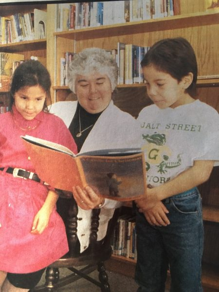 Sister Maureen Wallace reading to two children at school on Pleasant Point Indian Reservation.