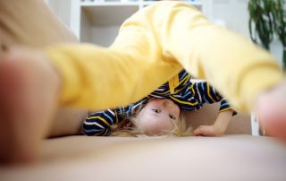 Little boy headstand on couch