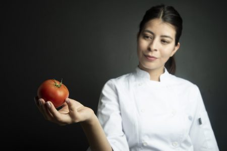 Chef looking at tomato/Adobe stock