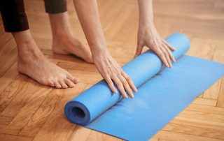Hands unrolling yoga mat